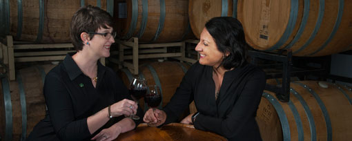 picture of two women smiling and holding wine glasses