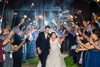 picture of bride and groom walking with people holding sparklers above them